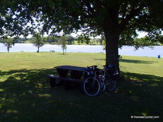 Atchison County Lake - Campsite - This is a typical campsite at Atchison County Lake, with a picnic table, grass, share, easy access to the lake, and nearby trash can.