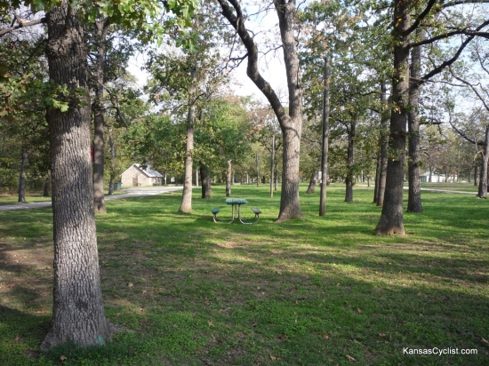 Camp Hunter - Camping Area - This is a view of one of the tent camping areas at Camp Hunter Park in Humboldt, Kansas. There are picnic tables, trash bins, and electricity nearby, with plenty of grass and shade trees.