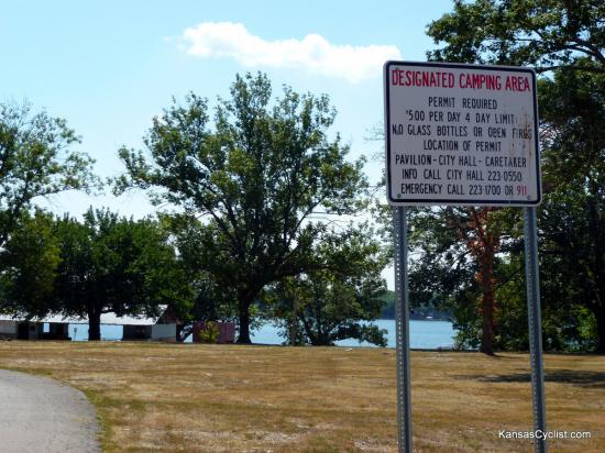 Lake Fort Scott - Designated Camping Area - This sign identifies the Designated Camping Area at Lake Fort Scott. Camping at the lake is allowed only in this area. The lake, picnic shelter, and restrooms are shown in the background.