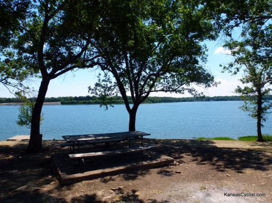 Lake Fort Scott - Campsite - This is a campsite at Lake Fort Scott, showing a picnic table and trash can. Campsites near the water are rocky and uneven, while sites farther from the water are generally flatter and grass-covered.