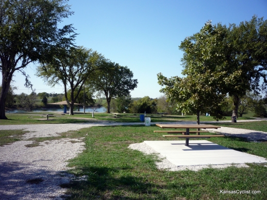 Garnett North Lake Park - Campground - This photo shows shows some of the campsites at North Lake Park in Garnett, Kansas. There are picnic tables, water and electricity, trash bins, a shelter, and grassy areas near the water.