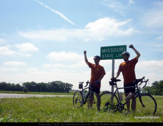 2011 Biking Across Kansas Finish Line - Two cyclists celebrate reaching the Missouri state line at the finish of the 2011 Biking Across Kansas tour. Near La Cygne, Kansas.