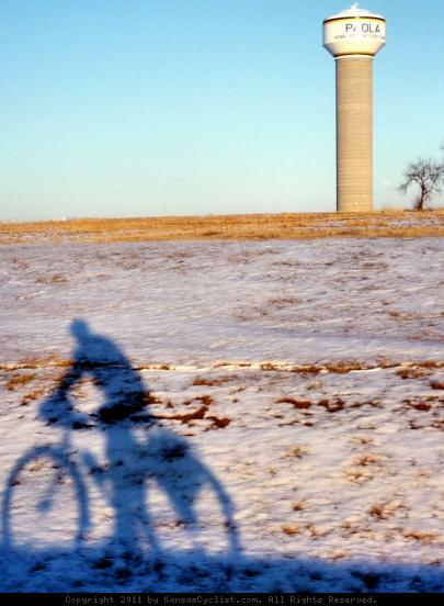 Paola Shadow Rider - A bicyclist rides through a snow-covered landscape in Paola, Kansas.