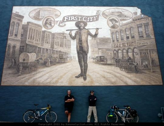Leavenworth First City Mural - Bicycle tourists pose beneath the 'First City' mural in Leavenworth, Kansas. The mural depicts 'Buffalo Bill', an early lawman in what was the first city incorporated in the state of Kansas.