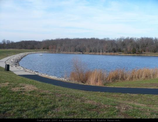 Kill Creek Park 2007 - Kill Creek Lake, a small 28-acre structure with a swimming beach and marina, viewed from the southwest corner of the dam, with paved pathway in the foreground.