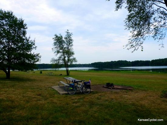 Louisburg Middle Creek State Fishing Lake - Campsite - A typical campsite at Louisburg Middle Creek State Fishing Lake, with a fire ring, picnic tables, grass, and some shade trees. There are approximately ten such sites available on the north shore of the lake.