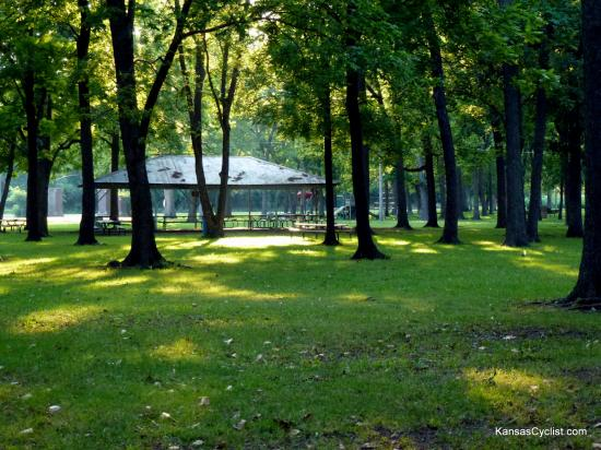 Neosho Falls Riverside Park - Picnic Shelter - A view of the trees and grass at Riverside Park, with picnic tables and a picnic shelter.