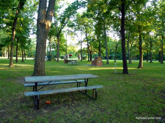 Neosho Falls Riverside Park - Picnic Tables - This photo shows some of the picnic tables and fireplaces, with playground equipment in the background.
