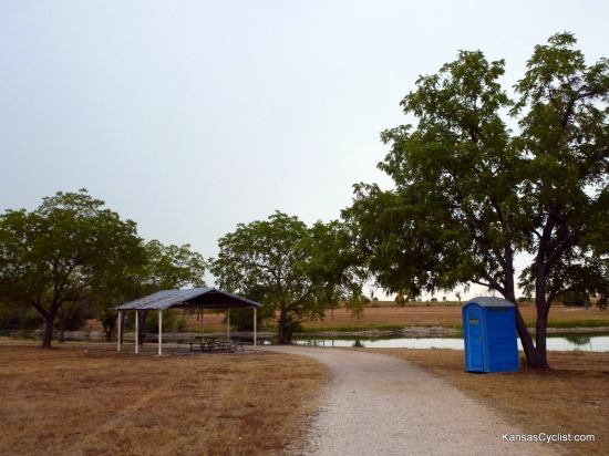 Richmond City Lake - Shelter - This photo shows one of the shelters at Richmond City Lake, along with a porta-potty, picnic tables, and grill. There is no drinking water or electricity available.