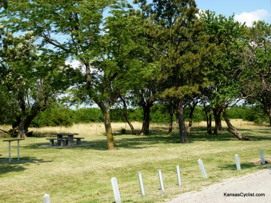US-54 Rosalia Roadside Park - This is a view of eastern end of the Rosalia Roadside Park, showing shade trees, grass for picnicking or camping, and a cement picnic table.