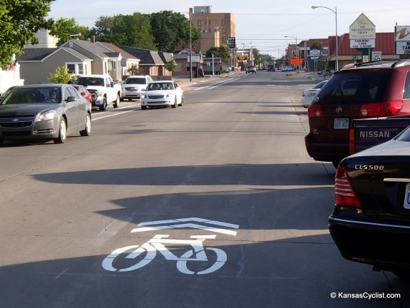 Sharrows on a street with front-in angle parking.