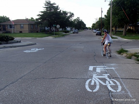 Sharrows with tilted chevrons indicate a turn in the bike route.