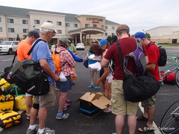Riders gather in Junction City to check in, load their bikes on the gear truck, and hop a bus to Hays.