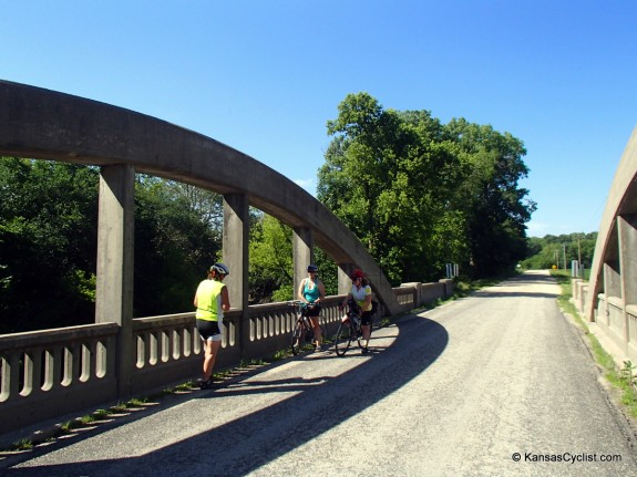 Cyclist chat at a historic rainbow arch bridge between Woodbine and Junction City.